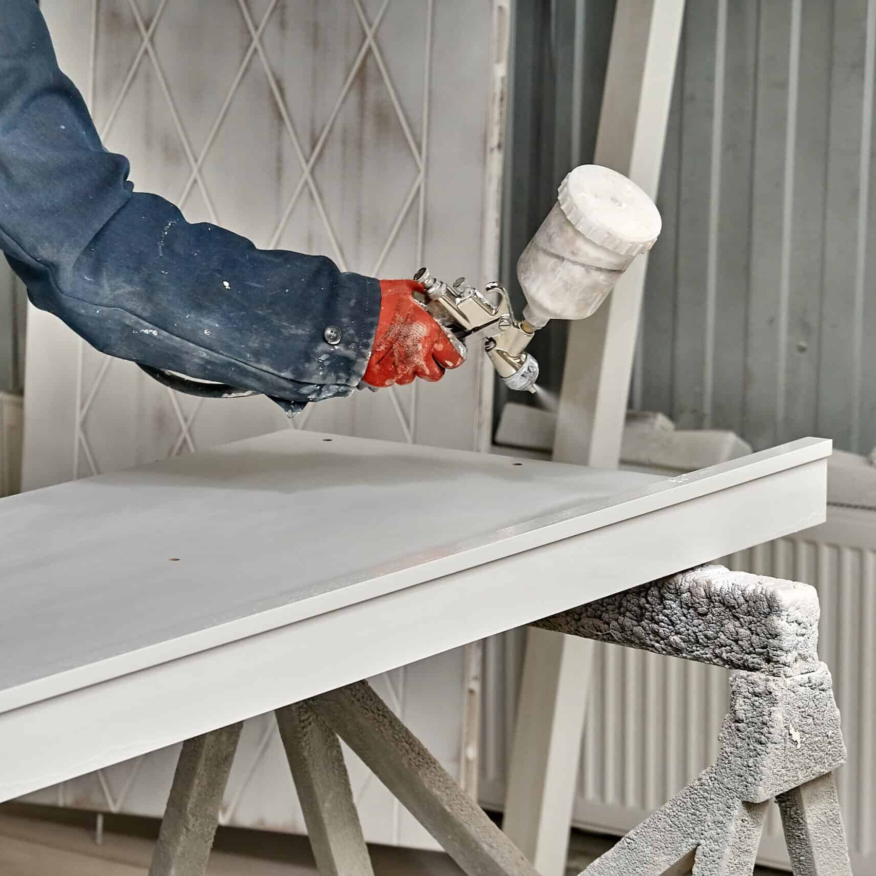 Painting cabinets with spray gun. Painting chamber, spray gun. Wooden furniture manufacturing process
