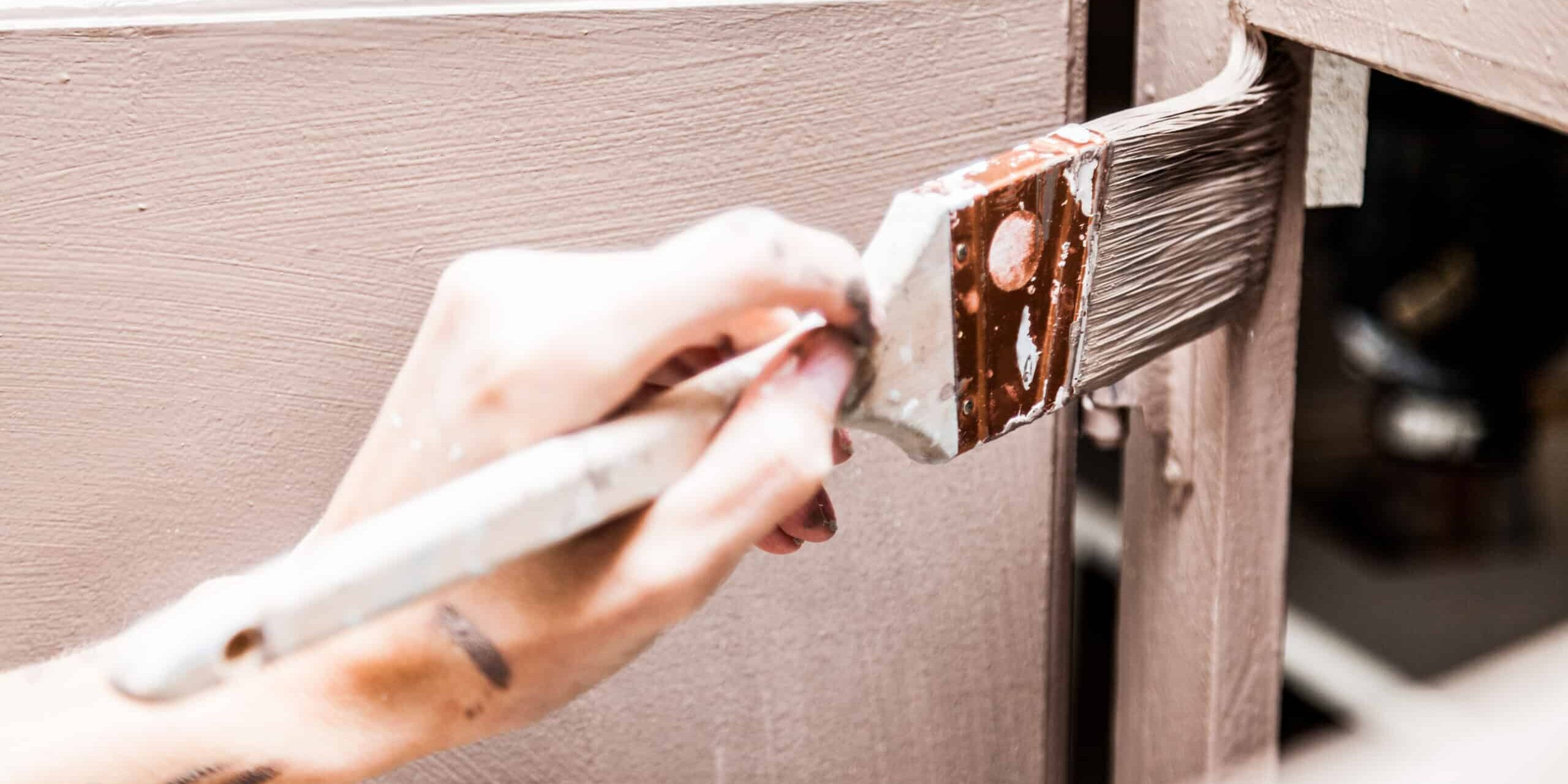 Closeup of Person Holding Paint Brush and Painting Kitchen Cabinets